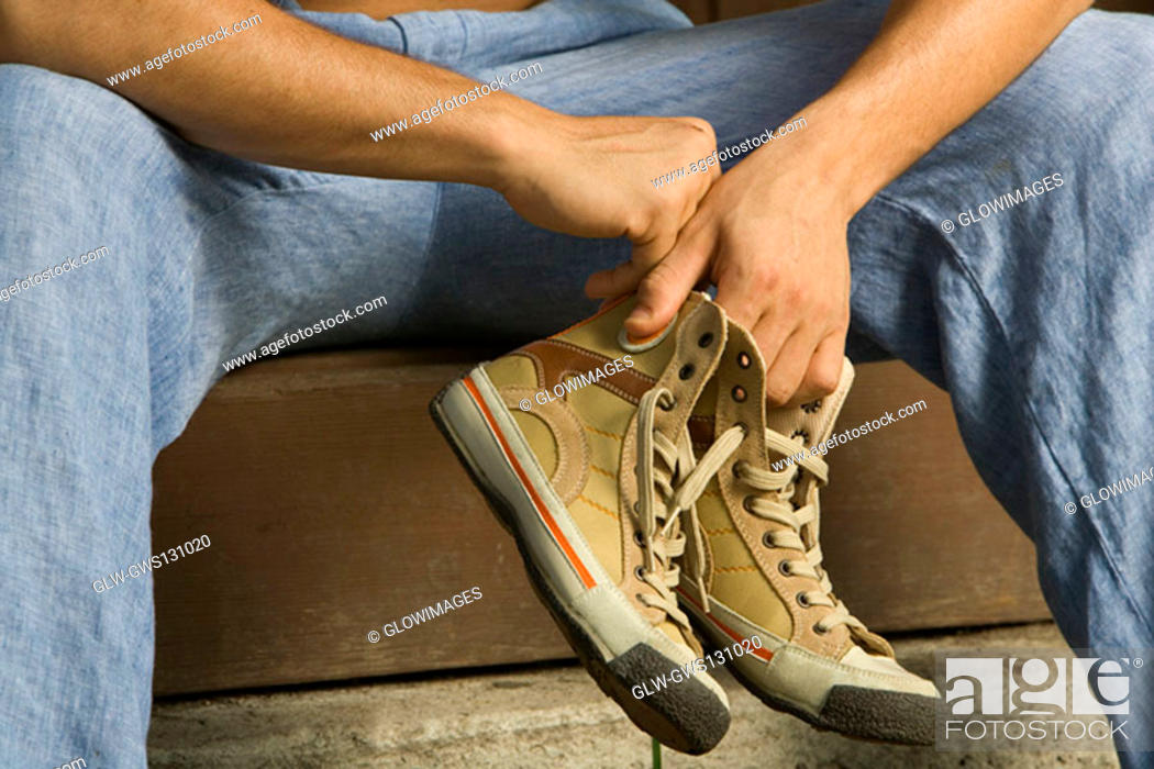 Stock Photo: Close-up of a person's hand holding a pair of canvas shoe.