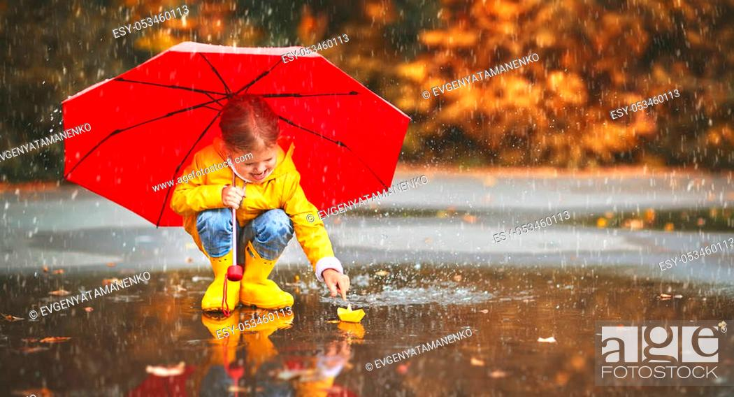 Stock Photo: happy child girl with umbrella and paper boat in a puddle in autumn on nature.