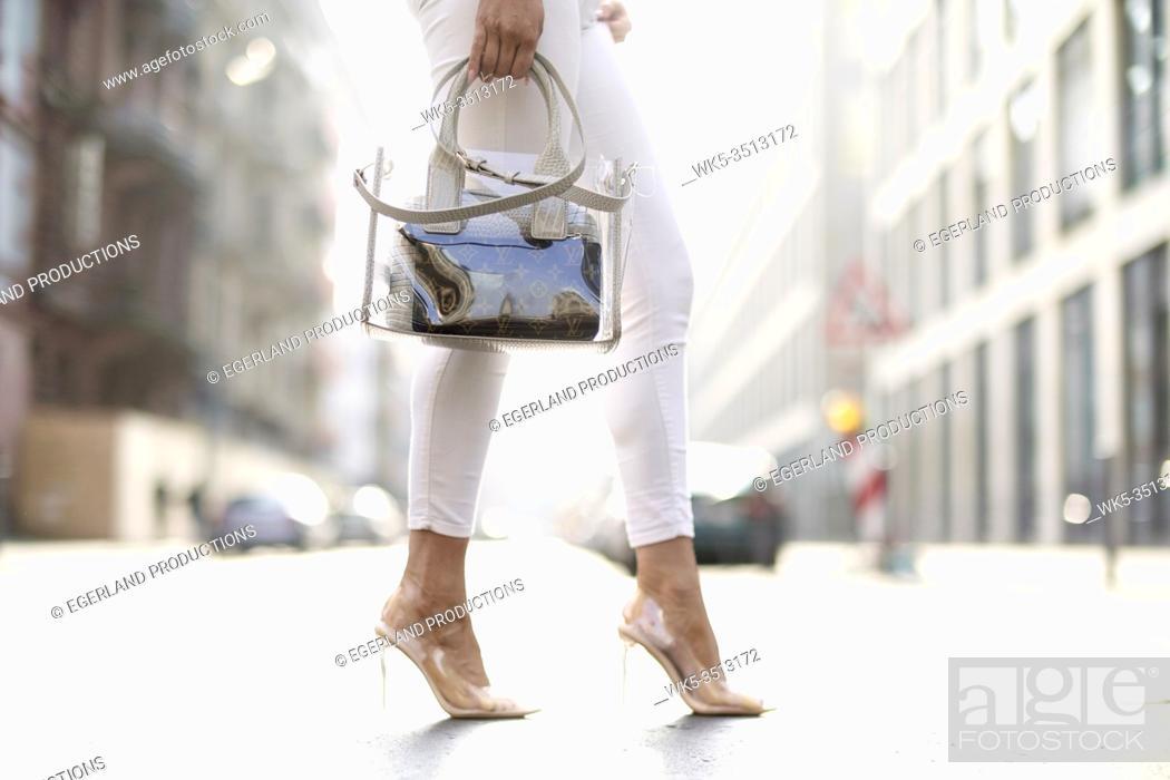 Stock Photo: legs of stylish woman and fashionable handbag.