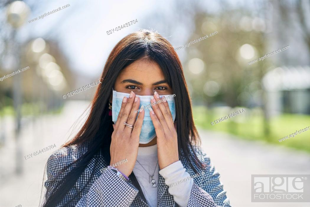 Stock Photo: Girl putting on a protective mask to avoid contagion while walking down the street. Coronavirus concept.