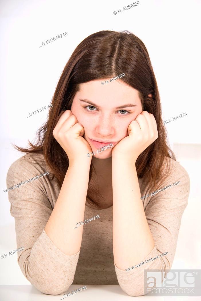 Stock Photo: Unhappy sulking teenage girl, elbows on table, had between hands.