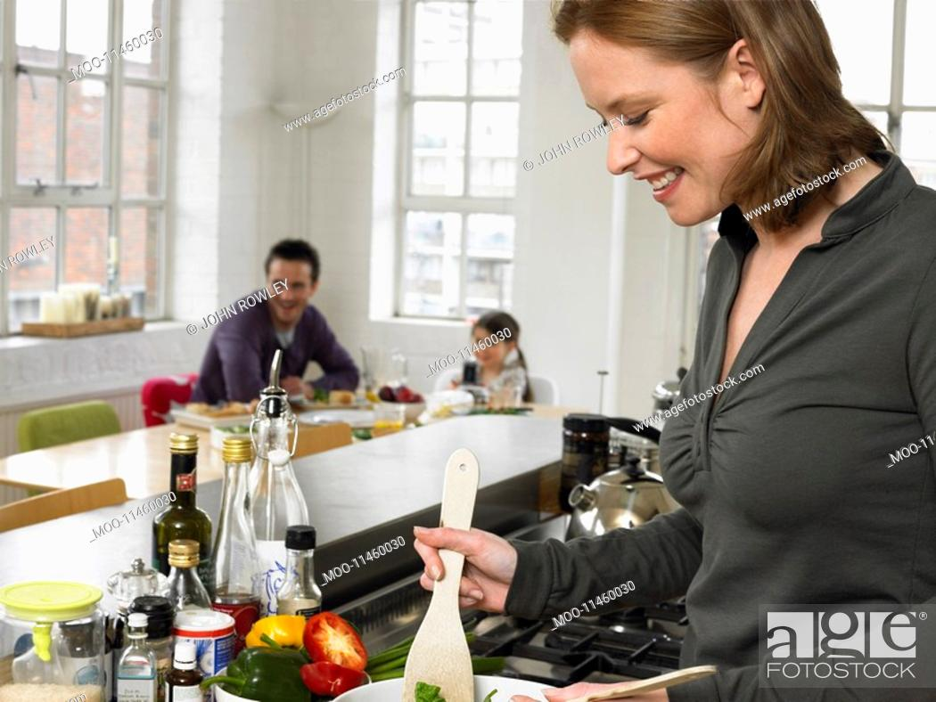 Stock Photo: Woman preparing salad in kitchen.