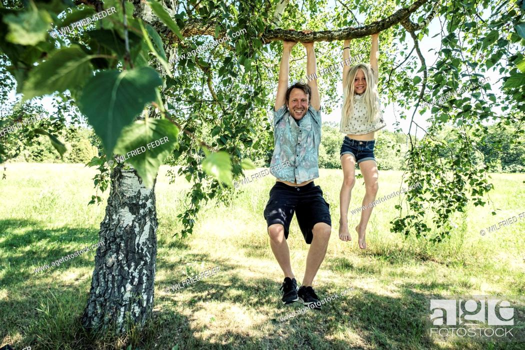 Stock Photo: Portrait of smiling father and daughter hanging on a branch of a birch tree.
