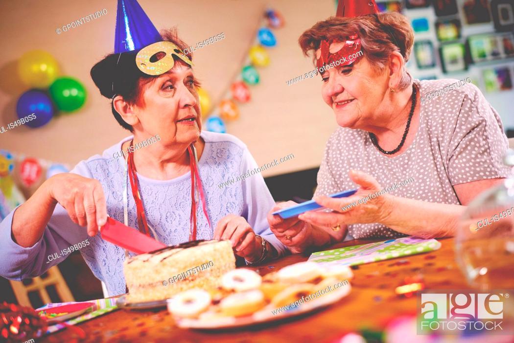 Stock Photo: Senior women serving birthday cake at party.