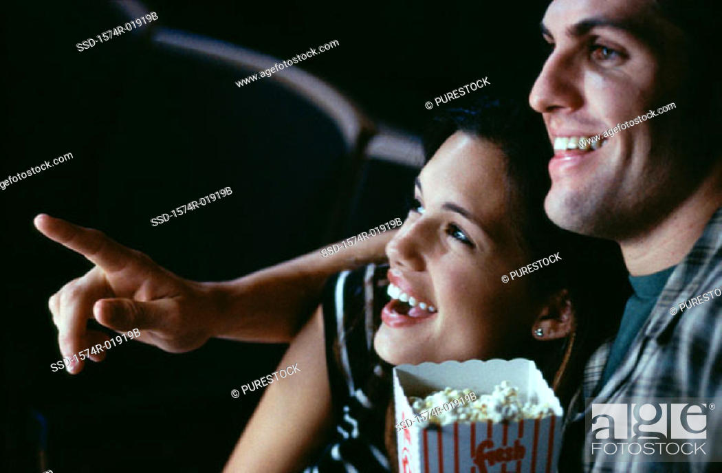 Stock Photo: Close-up of a young couple watching a movie in a theater.