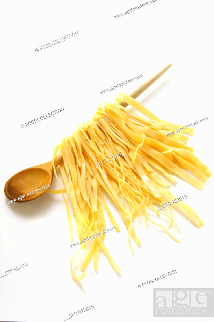 Stock Photo: Home-made pasta hanging on kitchen spoon.