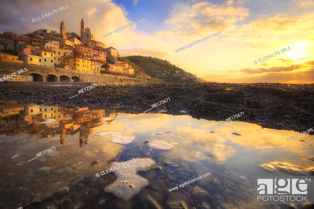 Stock Photo: The village is reflected in a puddle on the beach during the sunrise. Cervo, Imperia province, Liguria, Italy, Europe.