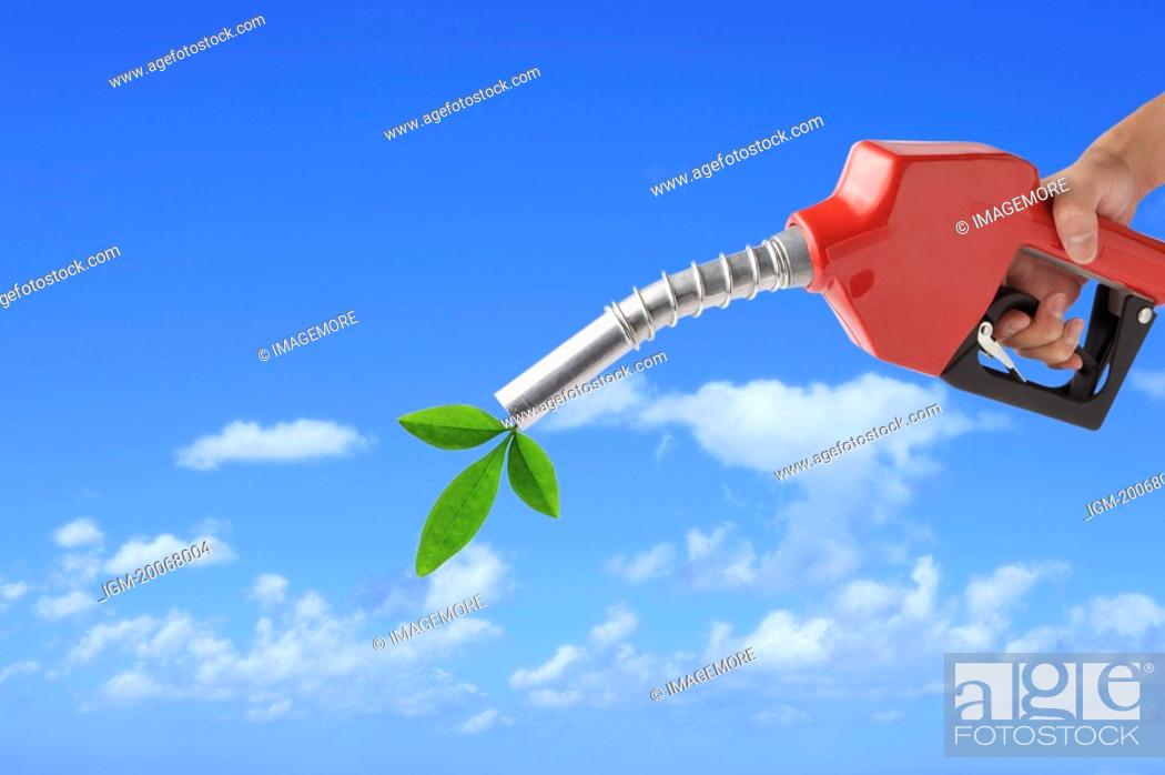 Stock Photo: Lohas, Environmental Conservation, Digitally generated image of human hand holding a fuel pump with a green leaf on the outlet.