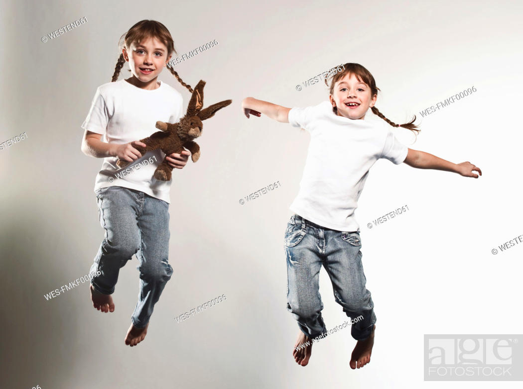 Stock Photo: Girls 6-7 jumping against gray background, smiling, portrait.