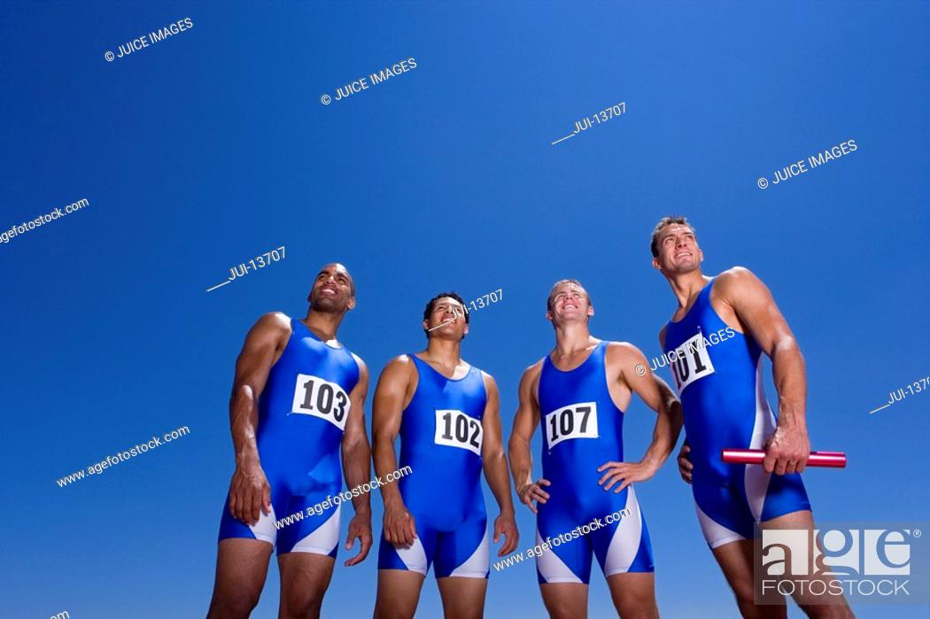 Stock Photo: Male athletes in row, smiling, low angle view.