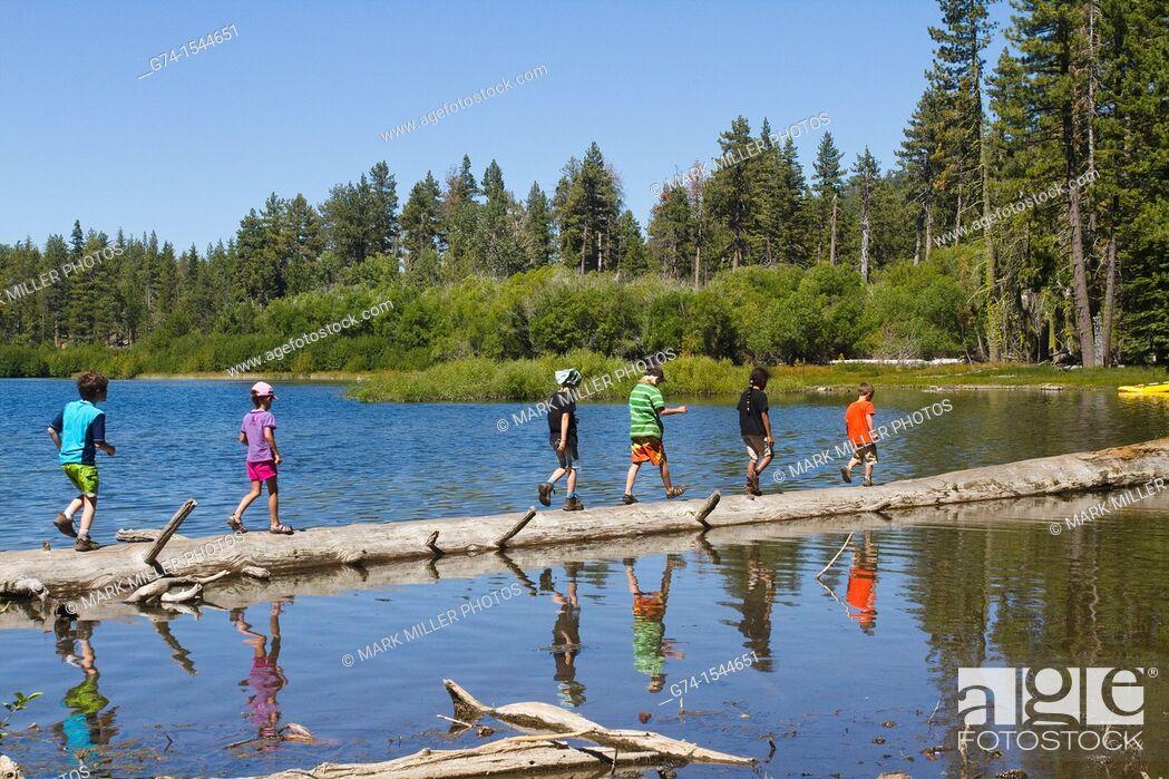 Stock Photo: Children on Log in Manzanita Lake, Lassen Volcanic National Park, California, USA.