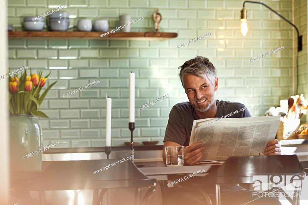 Stock Photo: Smiling mature man sitting in kitchen reading newspaper.