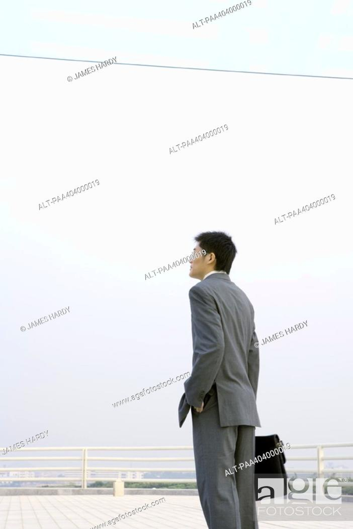 Stock Photo: Businessman standing with briefcase, on office building terrace.