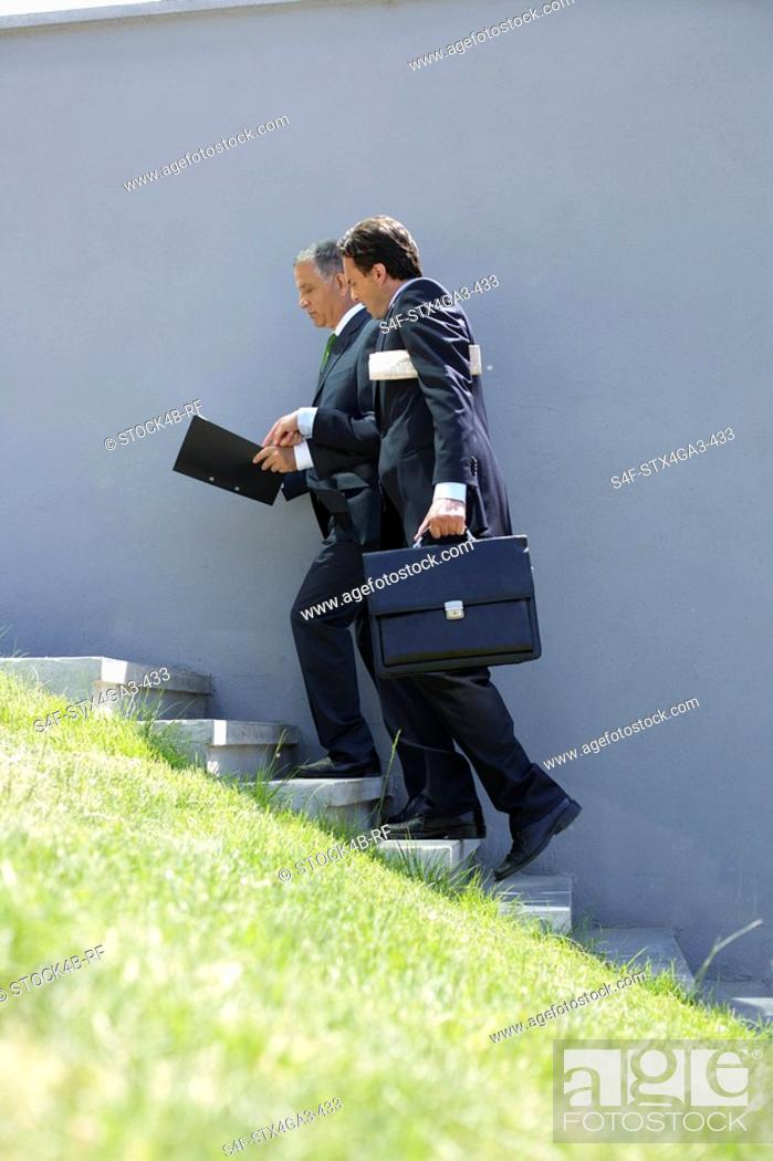Stock Photo: Two businessman going up a stairway.
