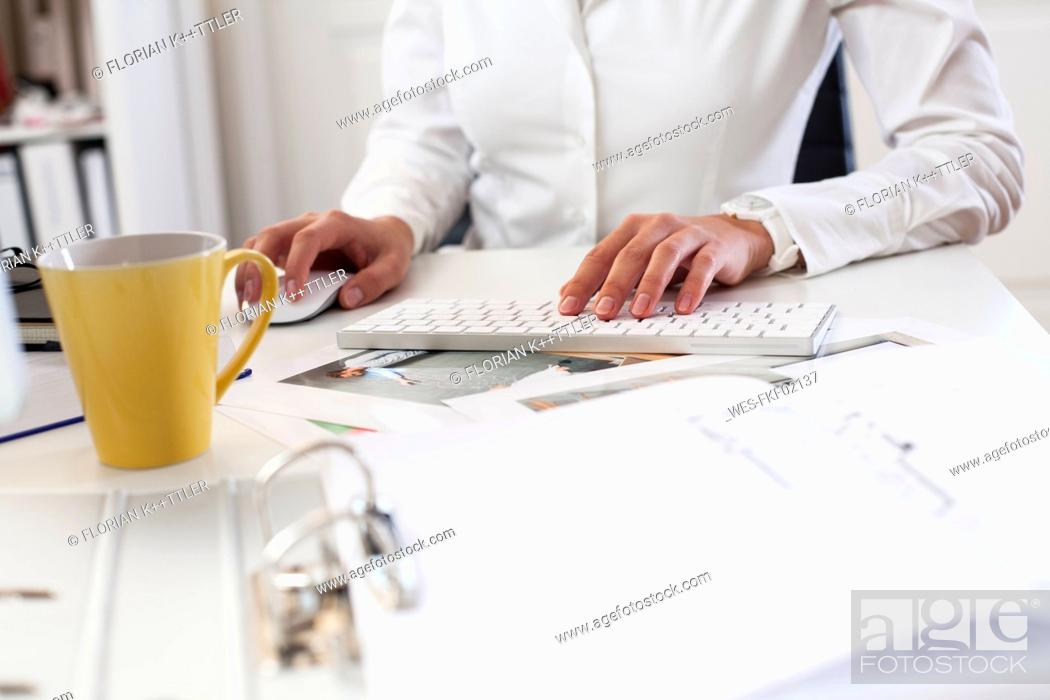 Stock Photo: Close-up of woman using computer keyboard in office.