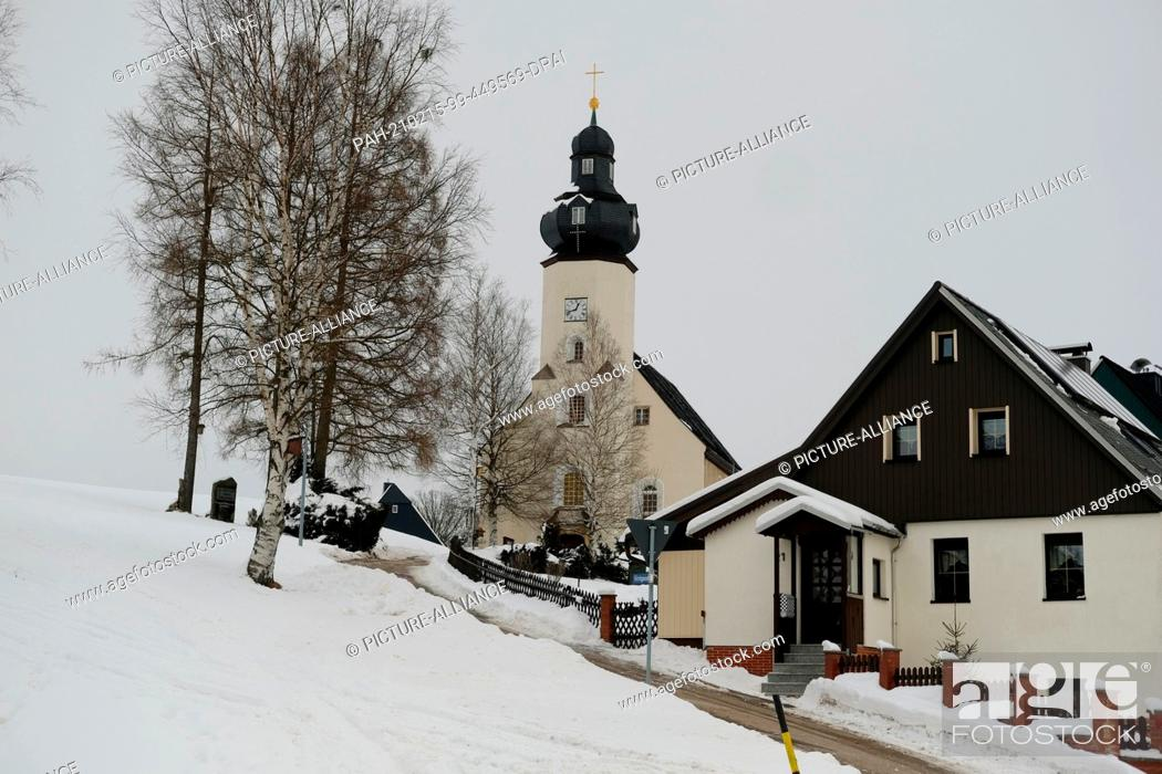 Stock Photo: 15 February 2021, Saxony, Kühnhaide: The church in Kühnhaide, a district of the Saxon town of Marienberg in the Erzgebirge district, is surrounded by snow.