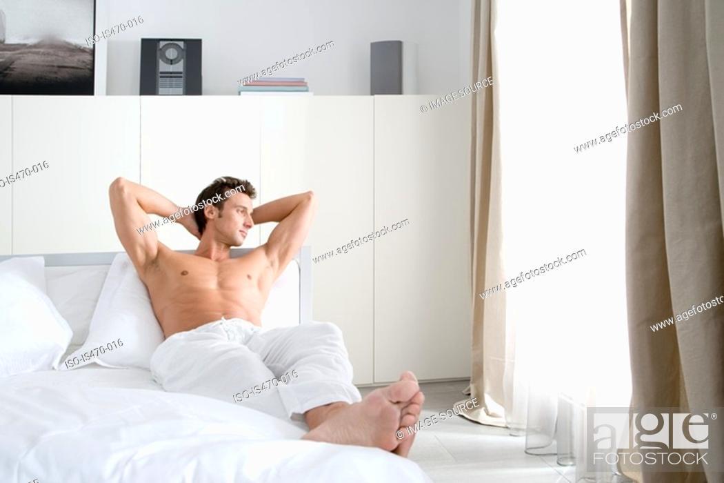 Stock Photo: Man relaxing in bedroom.