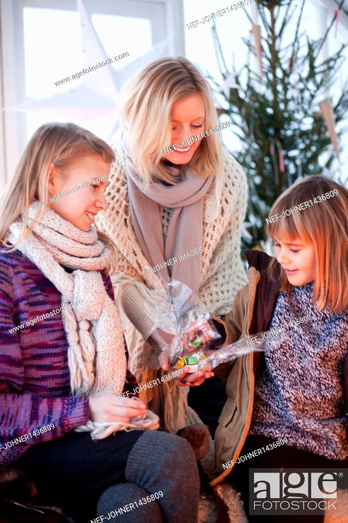 Imagen: Woman giving Christmas present to girls in greenhouse.