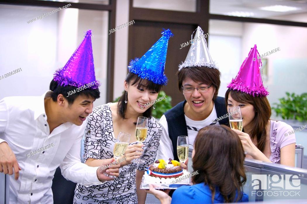 Stock Photo: Colleagues wearing party hats and holding drink to celebrate.
