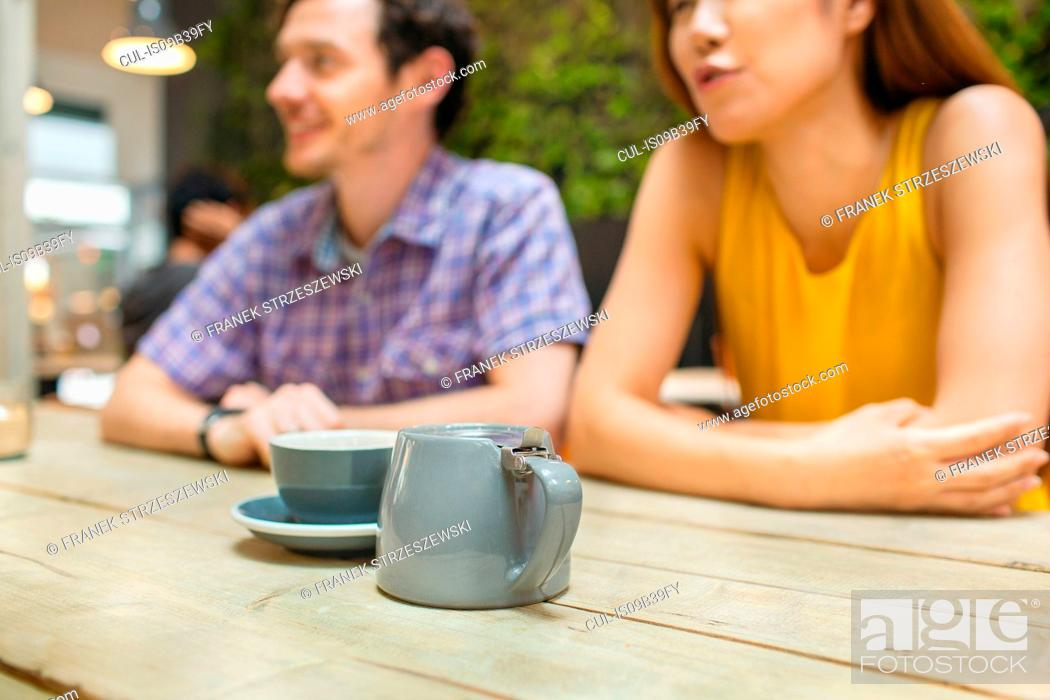 Stock Photo: Mid adult couple at coffee shop table.