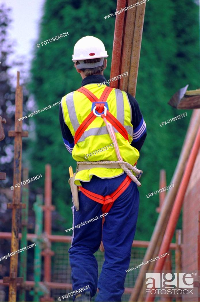 Stock Photo: Construction workers erecting a scaffolding.