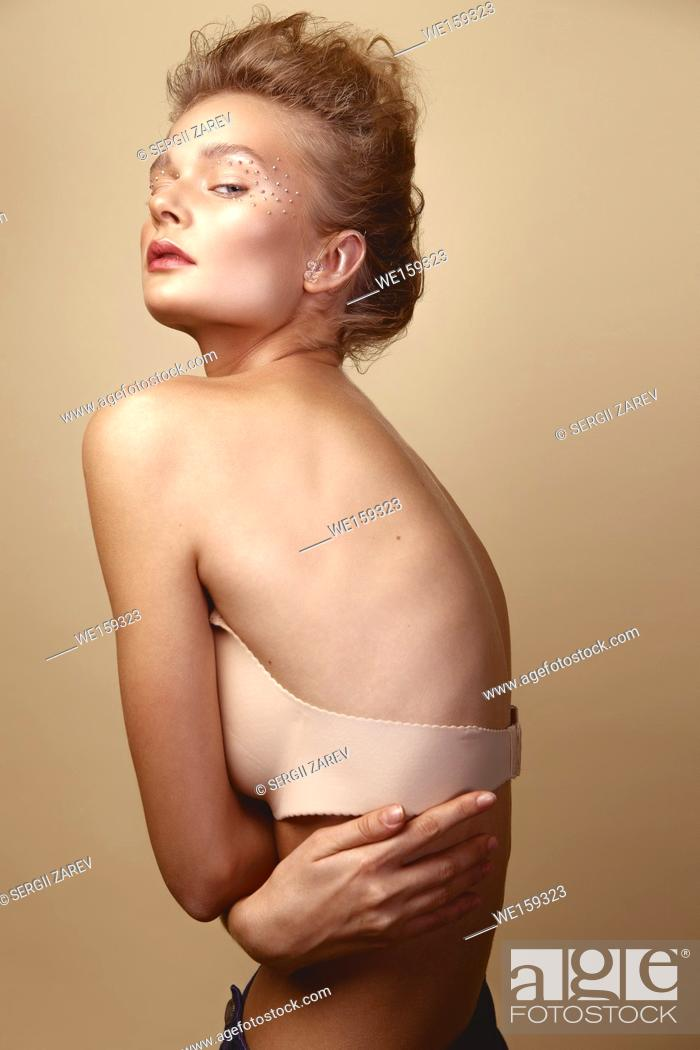 Stock Photo: Studio Portrait of a young cute blonde model girl in art makeup with rhinestones.