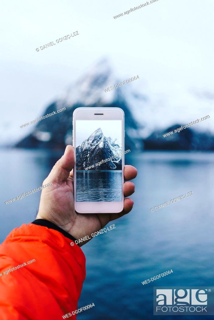 Stock Photo: Close-up of tourist taking a smartphone picture at Hamnoy, Lofoten, Norway.