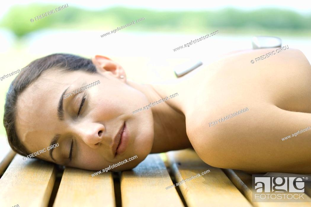 Stock Photo: Woman lying on deck with hot stones on back.
