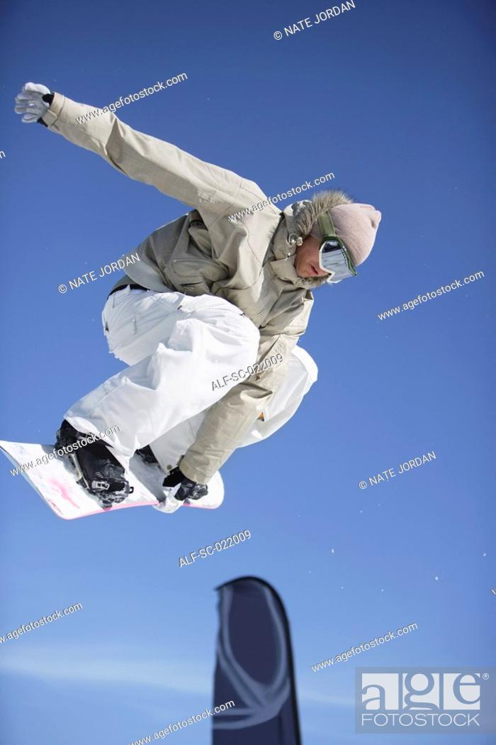 Stock Photo: Snowboarder Juping a Barrier.