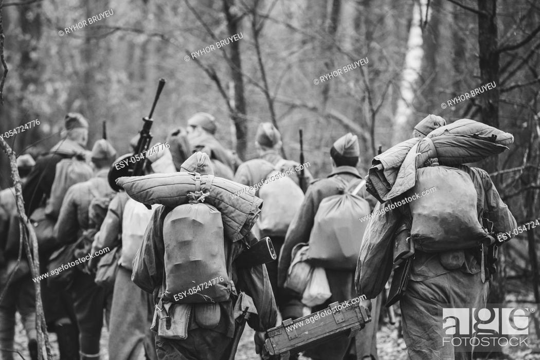 Stock Photo: Re-enactors Dressed As World War II Russian Soviet Red Army Soldiers Marching Through Forest In Autumn Day. Photo In Black And White Colors.