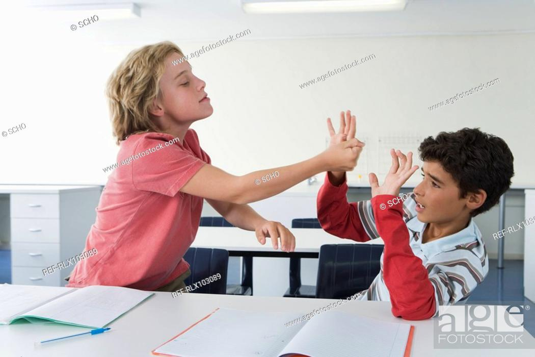 Stock Photo: School boys 10-13 in classroom fighting, one boy hitting the other, bullying.