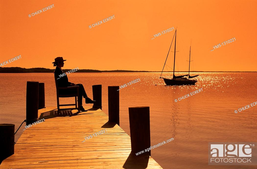 Stock Photo: Silhouette of woman waiting on island pier with sailboat.