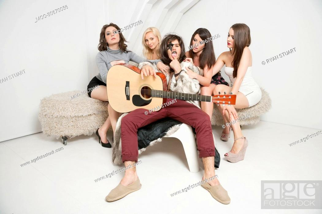 Stock Photo: Portrait of young male guitarist sitting amid young female friends.