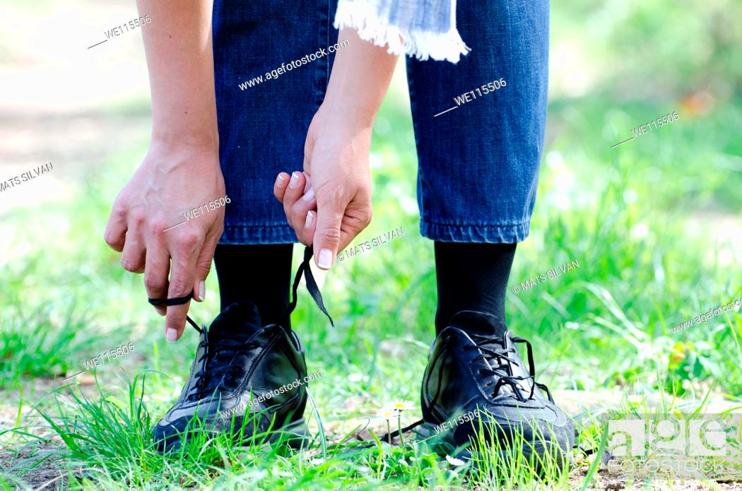 Stock Photo: Woman tying shoes on a path with grass.
