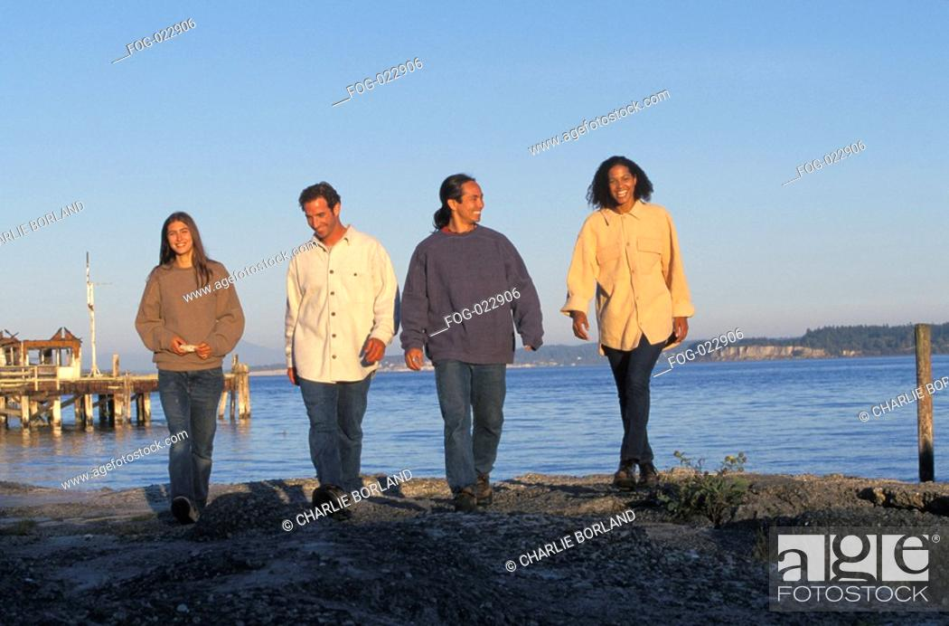Stock Photo: Group Of Friends Hiking Along The Lake Shore.