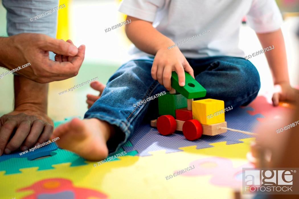 Stock Photo: Teacher and boy playing with toy train.