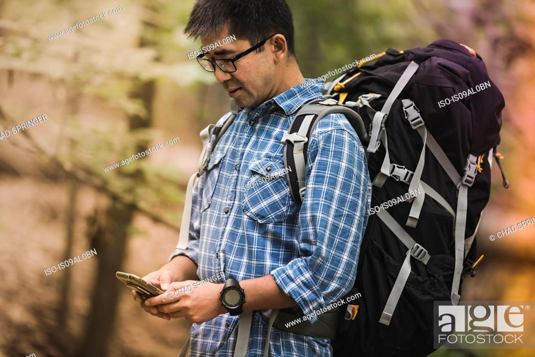 Stock Photo: Hiker with backpack, looking at smartphone.