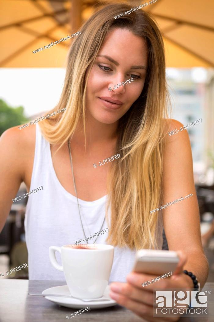 Stock Photo: Young woman in a street cafe checking her cell phone.