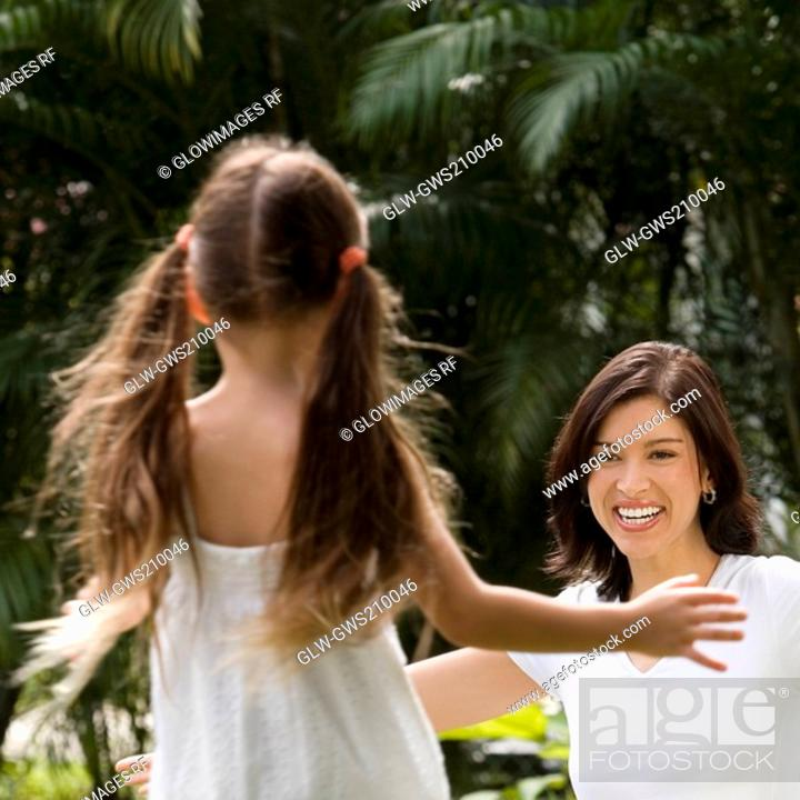 Stock Photo: Rear view of a girl running to hug her mother in a park.