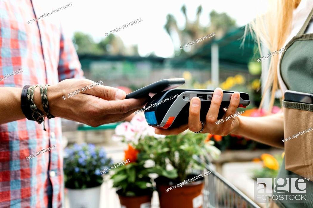 Stock Photo: Close-up of customer paying with smartphone in a garden center.