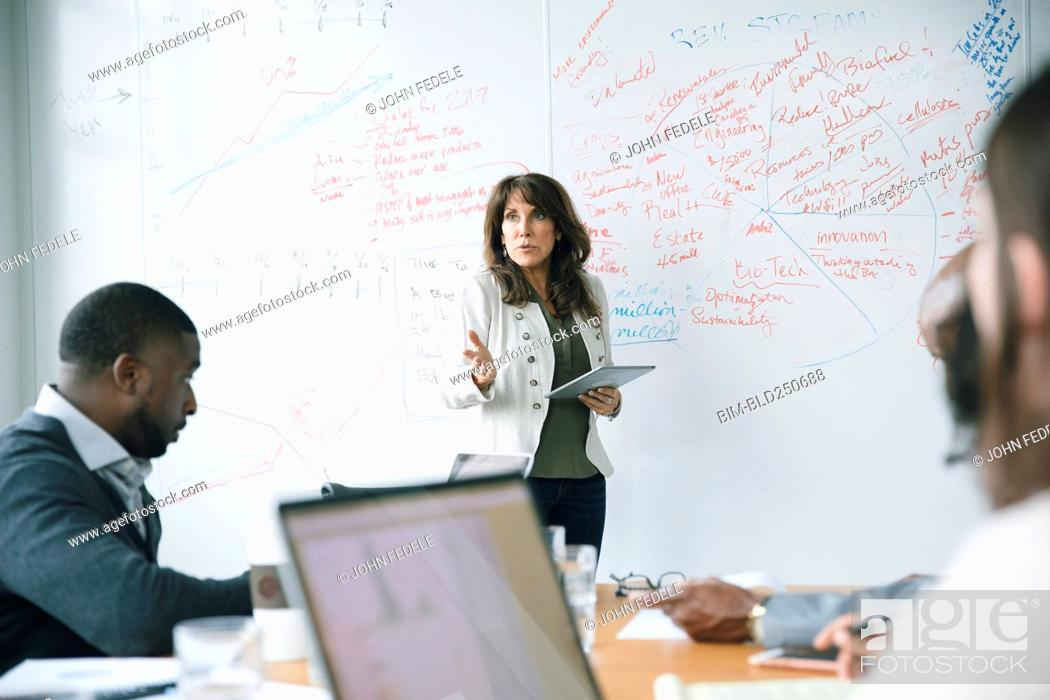 Stock Photo: Businesswoman holding digital tablet near whiteboard in meeting.