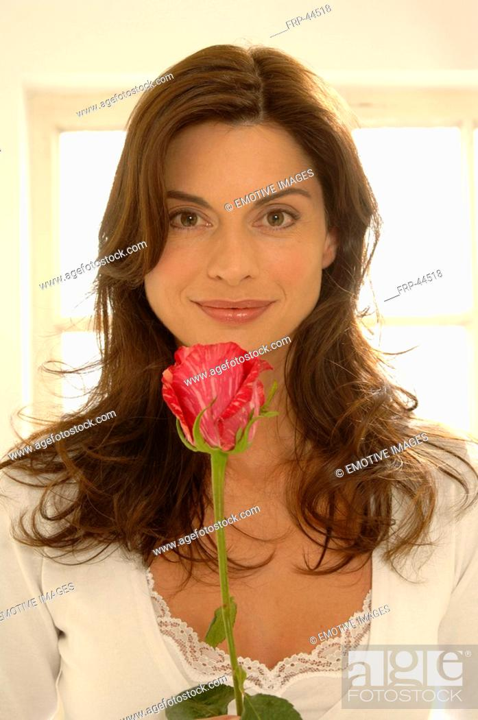 Stock Photo: Young woman with a single rose.