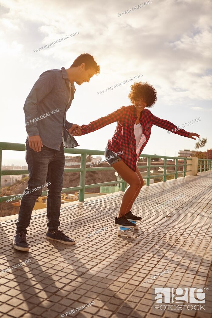 Stock Photo: Curly haired girl learning to skateboard while holding boy holds her hand tightly in great concentration while she looks down with her arms out.