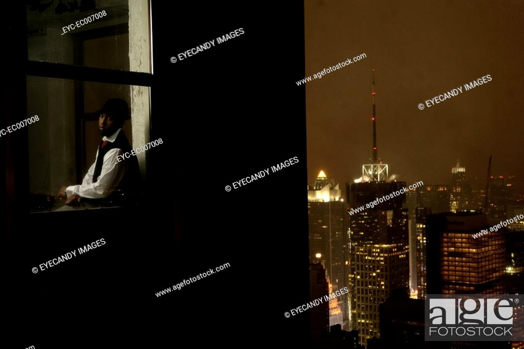 Stock Photo: Young man sitting in a window at night.