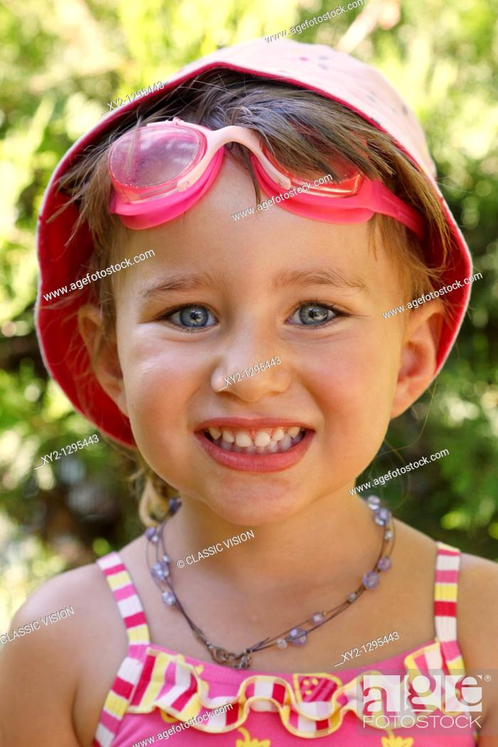 Stock Photo: Three year old girl wearing sun hat swimming goggles and swimsuit looking straight at camera and smiling.