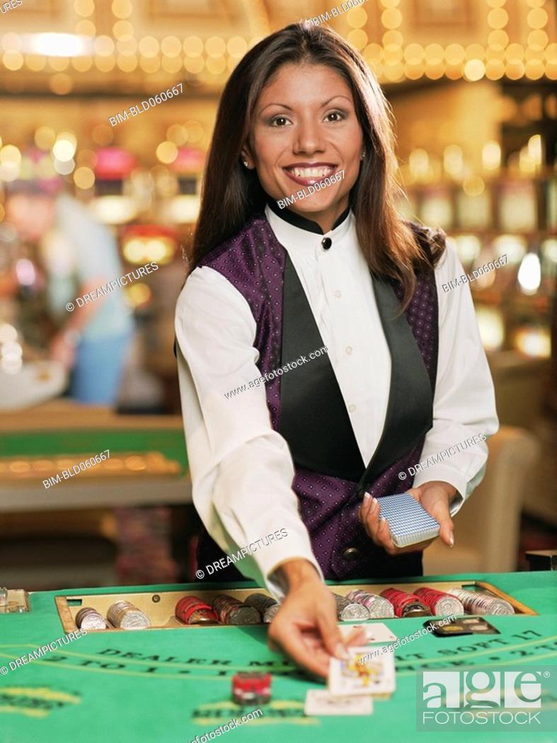 Stock Photo: Hispanic female blackjack dealer in casino.