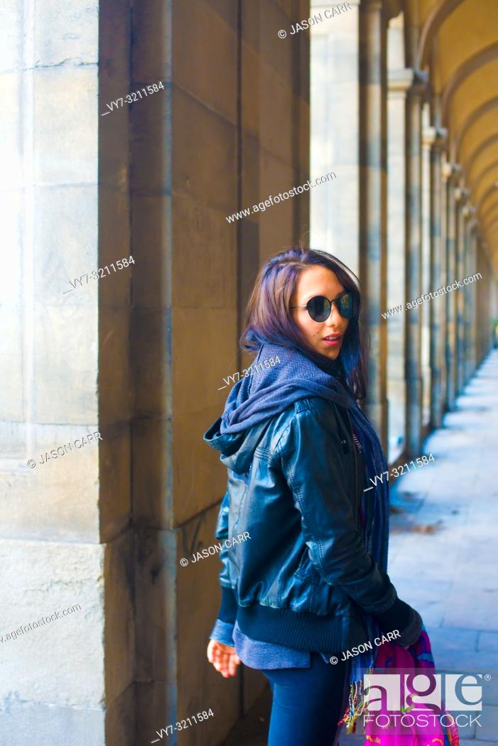 Stock Photo: Caucasian female model poses for pictures at the tourists destination Barcelona, Spain. Barcelona is known as an Artistic city located in the east coast of.