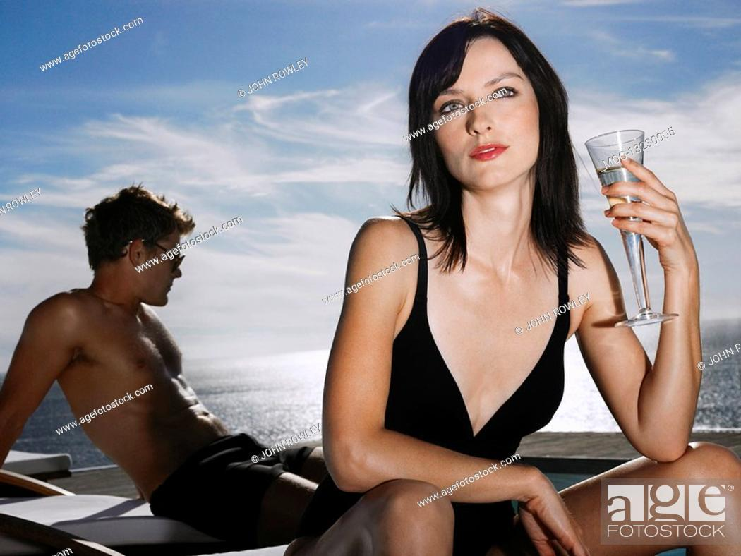 Stock Photo: Woman holding champagne glass man relaxing near sea.
