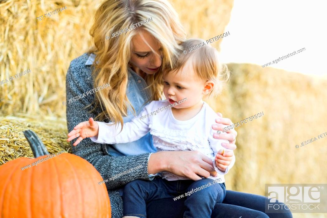 Stock Photo: Mother and daughter (12-17 months) looking at large pumpkin.