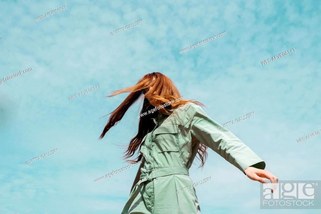 Stock Photo: Redheaded young woman dancing in front of sky.